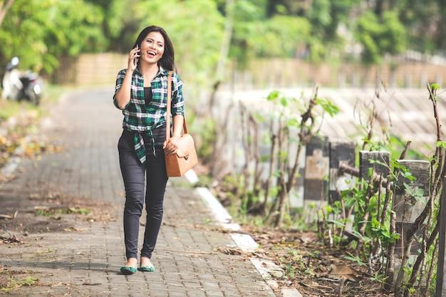 Jonge aziatische vrouw die op de telefoon spreekt terwijl het lopen op het pari