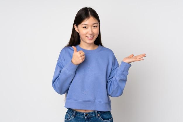 Jonge aziatische vrouw die op muur lege ruimte op de palm houden en met omhoog duimen