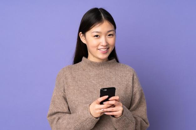 Jonge aziatische vrouw die op purpere muur een bericht met mobiel verzendt