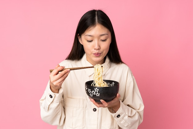 Jonge aziatische vrouw die op roze achtergrond wordt geïsoleerd die een kom noedels met eetstokjezand houdt dat het blaast omdat zij heet zijn