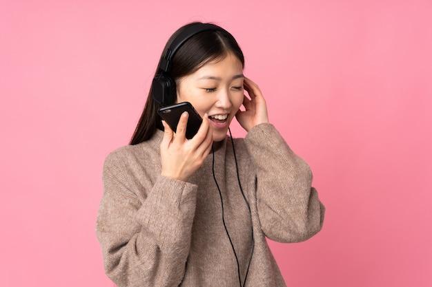 Jonge aziatische vrouw die op roze muur het luisteren muziek met mobiel en het zingen wordt geïsoleerd