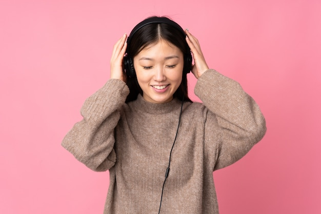 Jonge aziatische vrouw die op roze muur het luisteren muziek wordt geïsoleerd