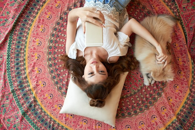 Jonge aziatische vrouw die op vloer thuis met smartphone en een kleine hond aaien