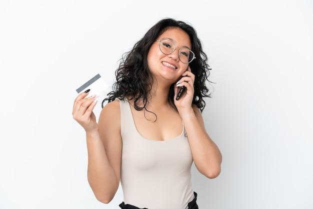 Jonge aziatische vrouw die op witte achtergrond een gesprek met de mobiele telefoon houdt en een creditcard houdt