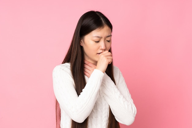 Jonge aziatische vrouw die over muur veel hoest