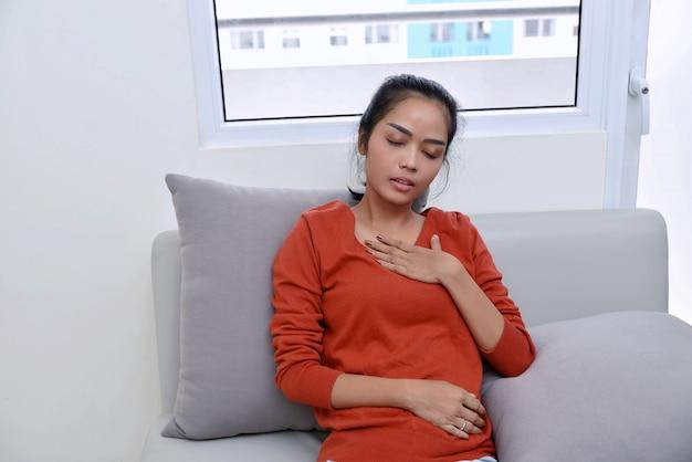 Jonge aziatische vrouw die pijn in haar borst voelt