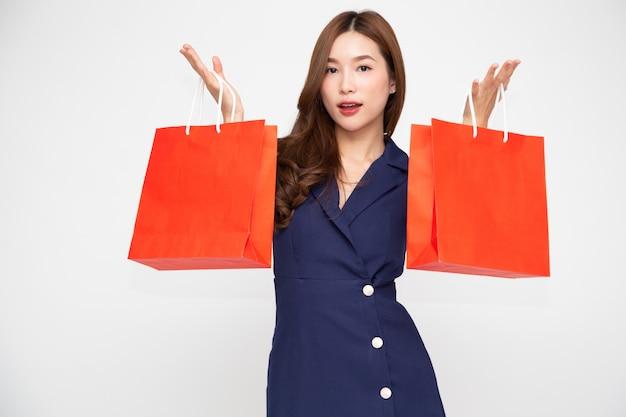Jonge aziatische vrouw die rode die het winkelen zakken houden op witte achtergrond worden geïsoleerd