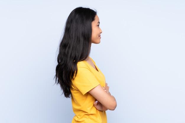 Jonge aziatische vrouw die roomijs over geïsoleerde achtergrond eet