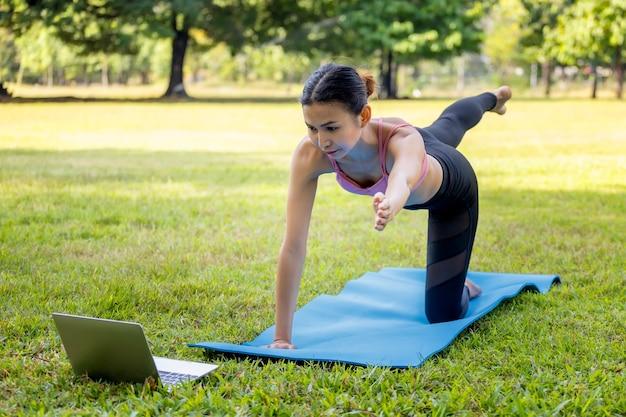 Jonge aziatische vrouw die 's ochtends yoga doet in het park op blauwe mat met laptop