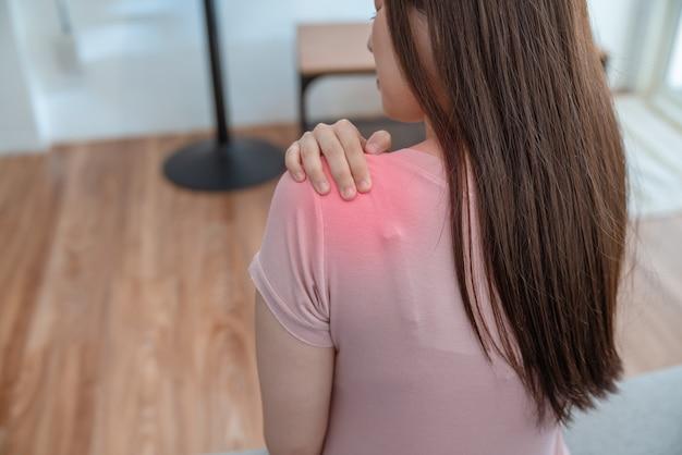 Jonge aziatische vrouw die schouderpijn lijdt