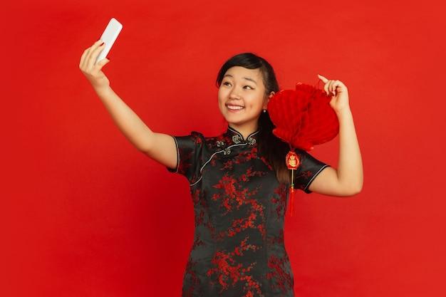 Jonge aziatische vrouw die selfie met chinese lantaarn neemt die op rode muur wordt geïsoleerd