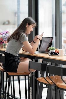 Jonge aziatische vrouw die smartphone en computer gebruikt terwijl ze in de co-werkruimte zit. verticale weergave.