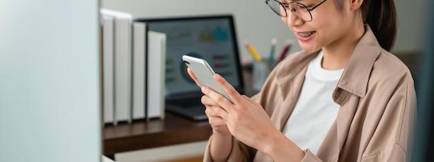 Jonge aziatische vrouw die smartphone houdt en online sociale levensstijl gebruikt
