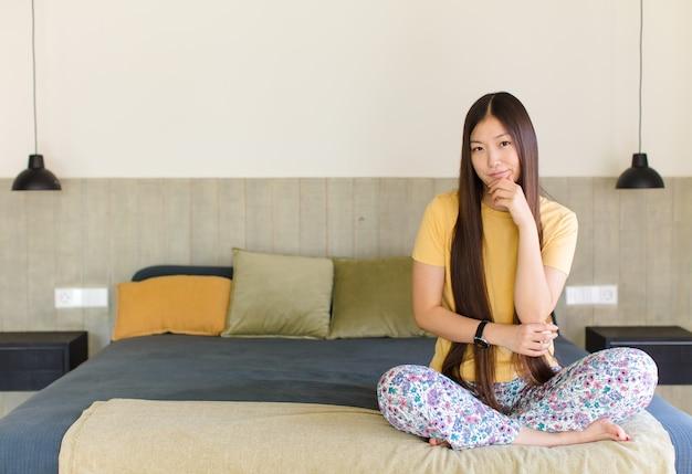 Jonge aziatische vrouw die succesvol en tevreden voelt, glimlachend met wijd open mond, ok teken met hand maakt
