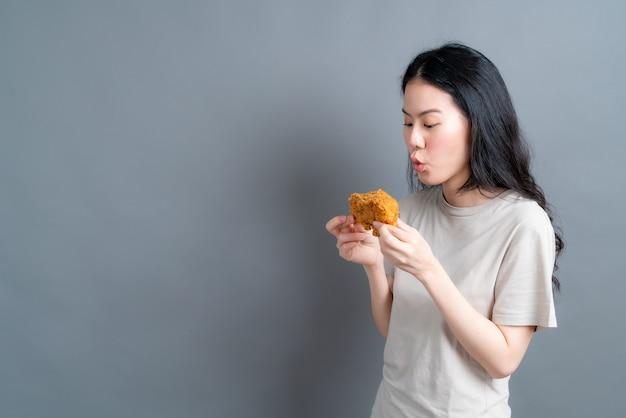 Jonge aziatische vrouw die t-shirt met een blij gezicht draagt en geniet van het eten van gebakken kip