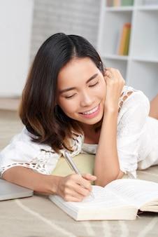 Jonge aziatische vrouw die tekst in haar boek merken die op vloer liggen