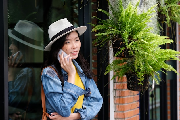 Jonge aziatische vrouw die telefoon op stads in openlucht achtergrond neemt