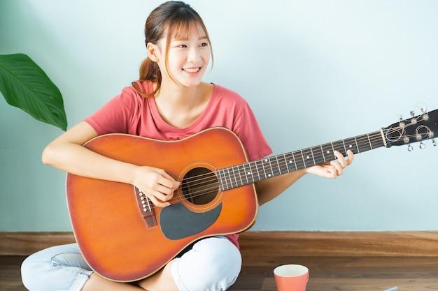 Jonge aziatische vrouw die thuis gitaar leert