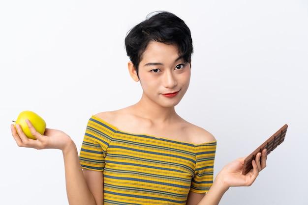 Jonge aziatische vrouw die twijfels hebben terwijl het nemen van een chocoladetablet in één hand en een appel in de andere