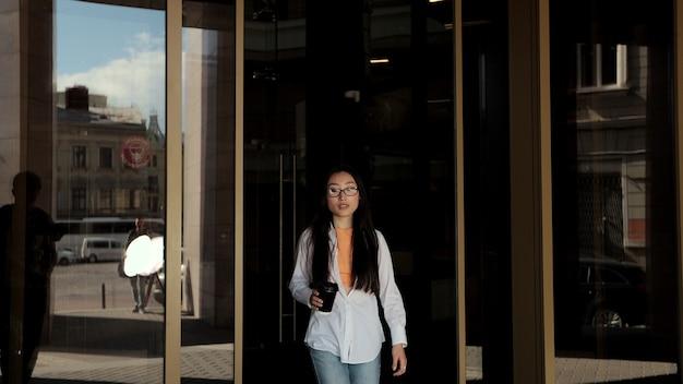 Jonge aziatische vrouw die uit het moderne gebouw gaat en koffie in de buitenlucht drinkt
