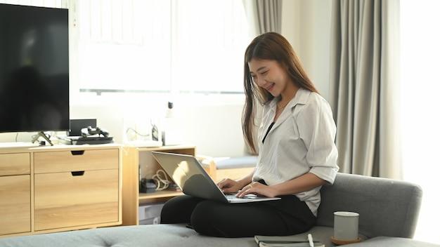 Jonge aziatische vrouw die van huis aan laptop werkt
