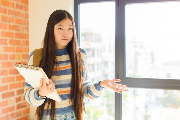 Jonge aziatische vrouw die verbaasd, verward en gestrest kijkt, zich afvraagt tussen verschillende opties, zich onzeker voelt