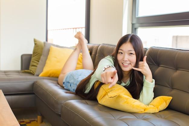 Jonge aziatische vrouw die vrolijk glimlacht en naar camera richt terwijl het u later gebaren maakt, pratend aan de telefoon