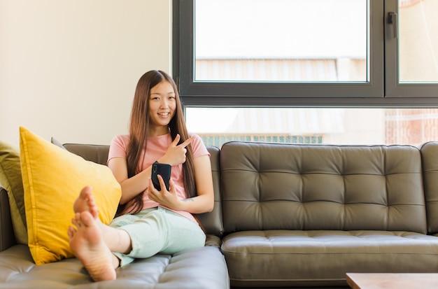 Jonge aziatische vrouw die vrolijk glimlacht, zich gelukkig voelt en naar de zijkant en naar boven wijst, voorwerp in exemplaarruimte toont