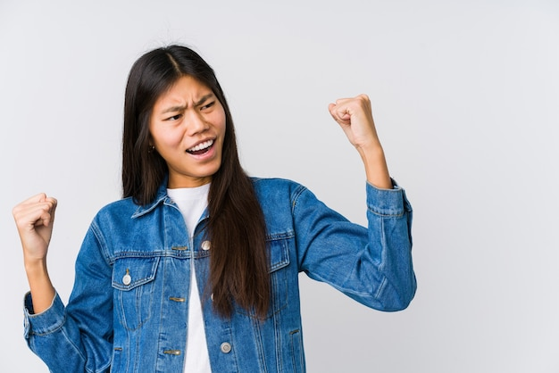 Jonge aziatische vrouw die vuist opheft na een overwinning, winnaarconcept.