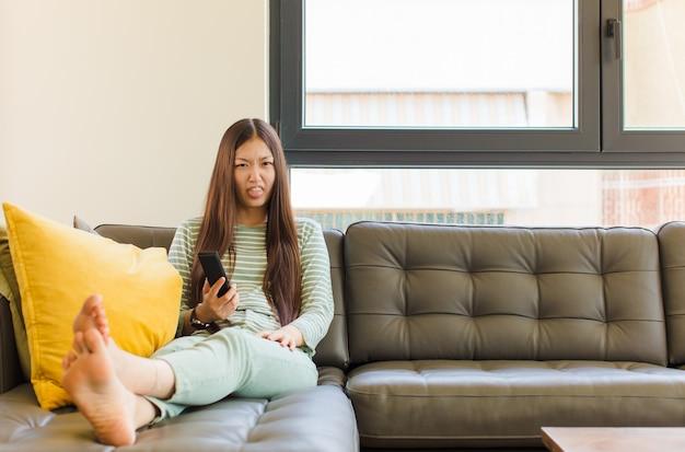 Jonge aziatische vrouw die walgt en geïrriteerd voelt, tong uitsteekt, niet van iets smerigs en vies houdt