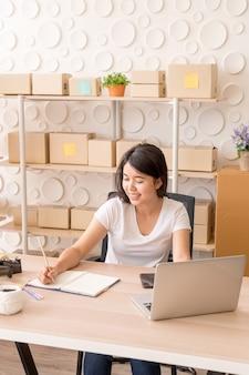 Jonge aziatische vrouw die werkt met digitale tablet op de werkplek