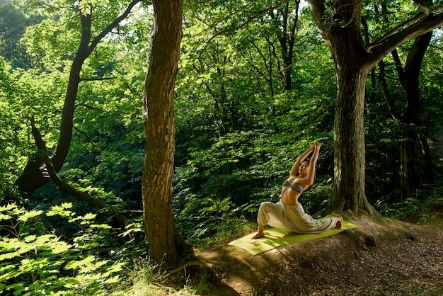 Jonge aziatische vrouw die yoga in ochtendpark doen uitwerken, die etnische broek, bustehouder, binnen volledige lengte dragen.
