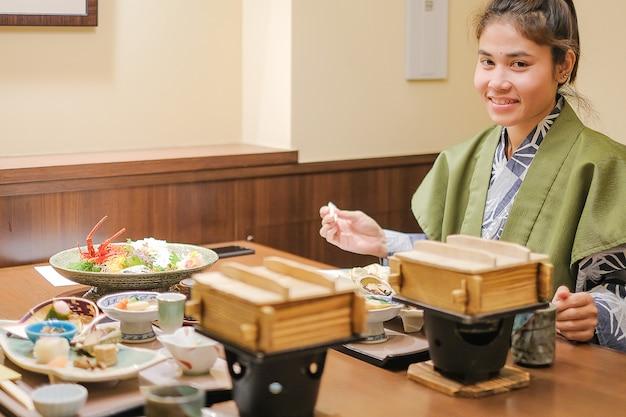 Jonge aziatische vrouw die yukata met japanse dinerreeks draagt