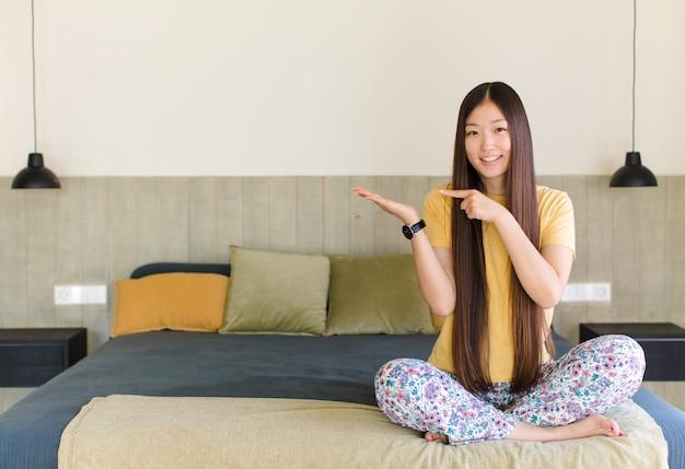 Jonge aziatische vrouw die, zelfverzekerd, succesvol en gelukkig glimlacht, concept of idee op exemplaarruimte aan de zijkant toont