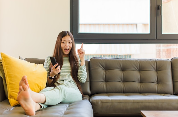 Jonge aziatische vrouw die zich als een gelukkig en opgewonden genie voelt na het realiseren van een idee, vrolijk vinger opheffend, eureka!