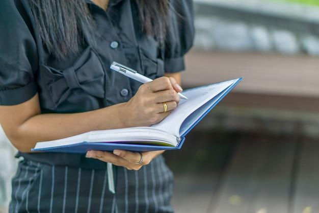 Jonge aziatische vrouw die zich bij het park bevindt en een notitieboekje schrijft. onderwijs concept.