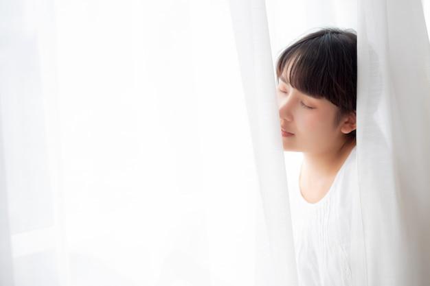 Jonge aziatische vrouw die zich dichtbij het venster bevindt