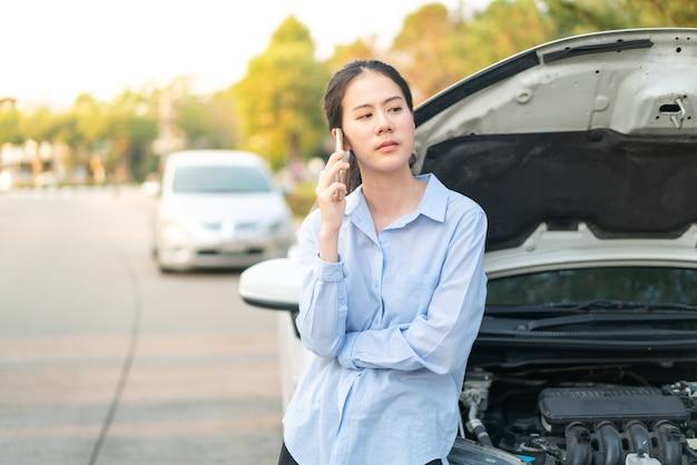 Jonge aziatische vrouw die zich dichtbij kapotte auto bevindt met opgedoken kap die problemen met haar voertuig heeft