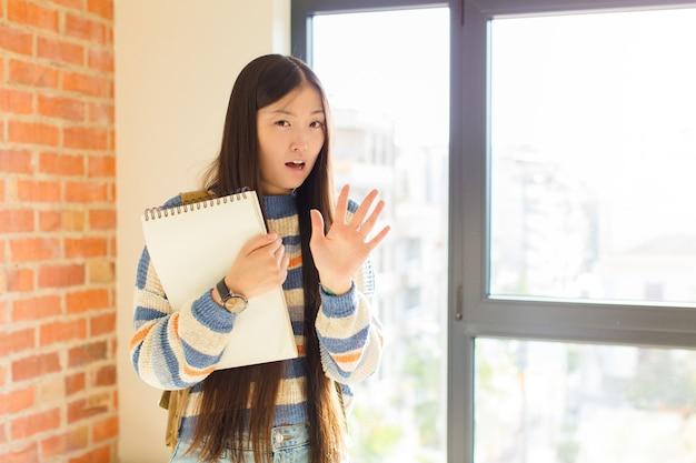 Jonge aziatische vrouw die zich doodsbang voelt, zich terugtrekt en schreeuwt van afgrijzen en paniek, reageert op een nachtmerrie