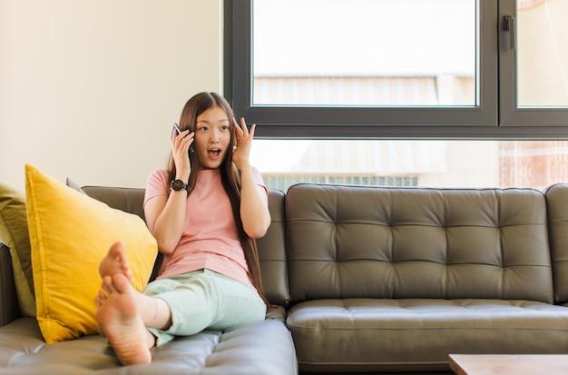 Jonge aziatische vrouw die zich gelukkig, opgewonden en verrast voelt, naar de kant kijkend met beide handen op het gezicht