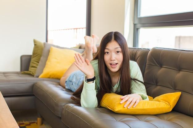 Jonge aziatische vrouw die zich gelukkig, verrast en opgewekt voelt, glimlachend met een positieve houding, een oplossing of een idee realiserend