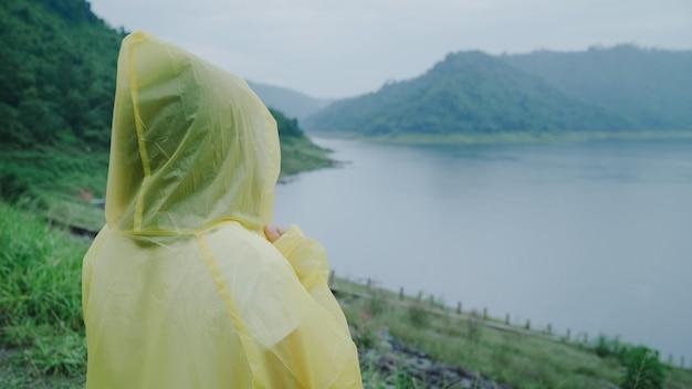 Jonge aziatische vrouw die zich gelukkig voelt als ze regen speelt terwijl ze een regenjas draagt die in de buurt van het meer staat