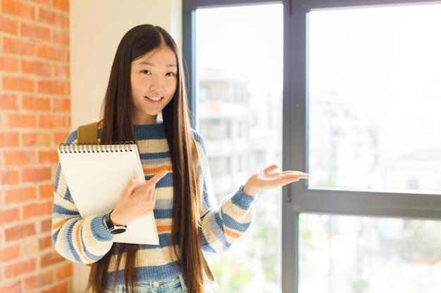 Jonge aziatische vrouw die, zich gelukkig, zorgeloos en tevreden glimlacht, wijzend naar concept of idee op exemplaarruimte aan de zijkant