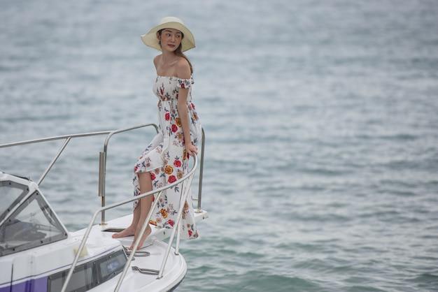 Jonge aziatische vrouw die zich op de voorzijde van het bootdek bevindt dat een brede overzeese mening met wind lang haar onderzoekt.