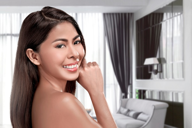 Jonge aziatische vrouw die zich op woonkamer bevindt
