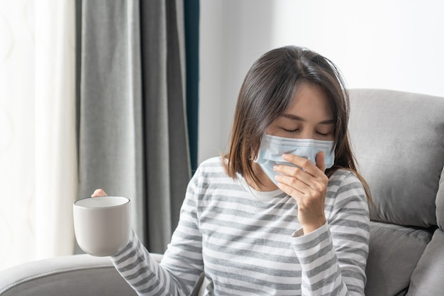 Jonge aziatische vrouw die zich thuis ziek voelt van verkoudheid en koorts, ziek meisje met gezichtsmasker heeft hoofdpijn en hoest op de bank in de woonkamer. gezondheidsproblemen concept.