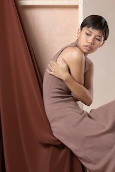 Jonge aziatische vrouw die zich voordeed in herfstkleren