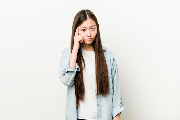 Jonge aziatische vrouw die zijn tempel met vingers richt