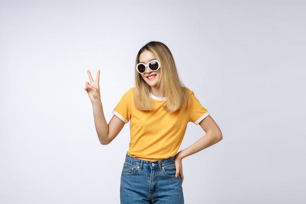 Jonge aziatische vrouw die zonnebril draagt die en met vingers toont benadrukt