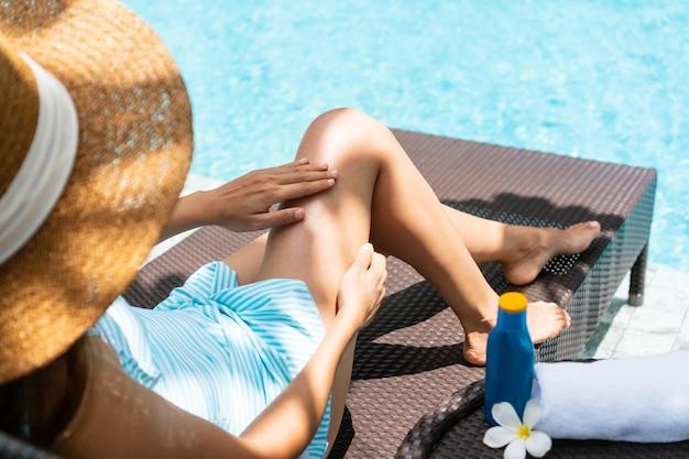 Jonge aziatische vrouw die zwempak draagt, hoed die op zonnebank zonnebrandcrème toepast en bij het zwembad ontspant.